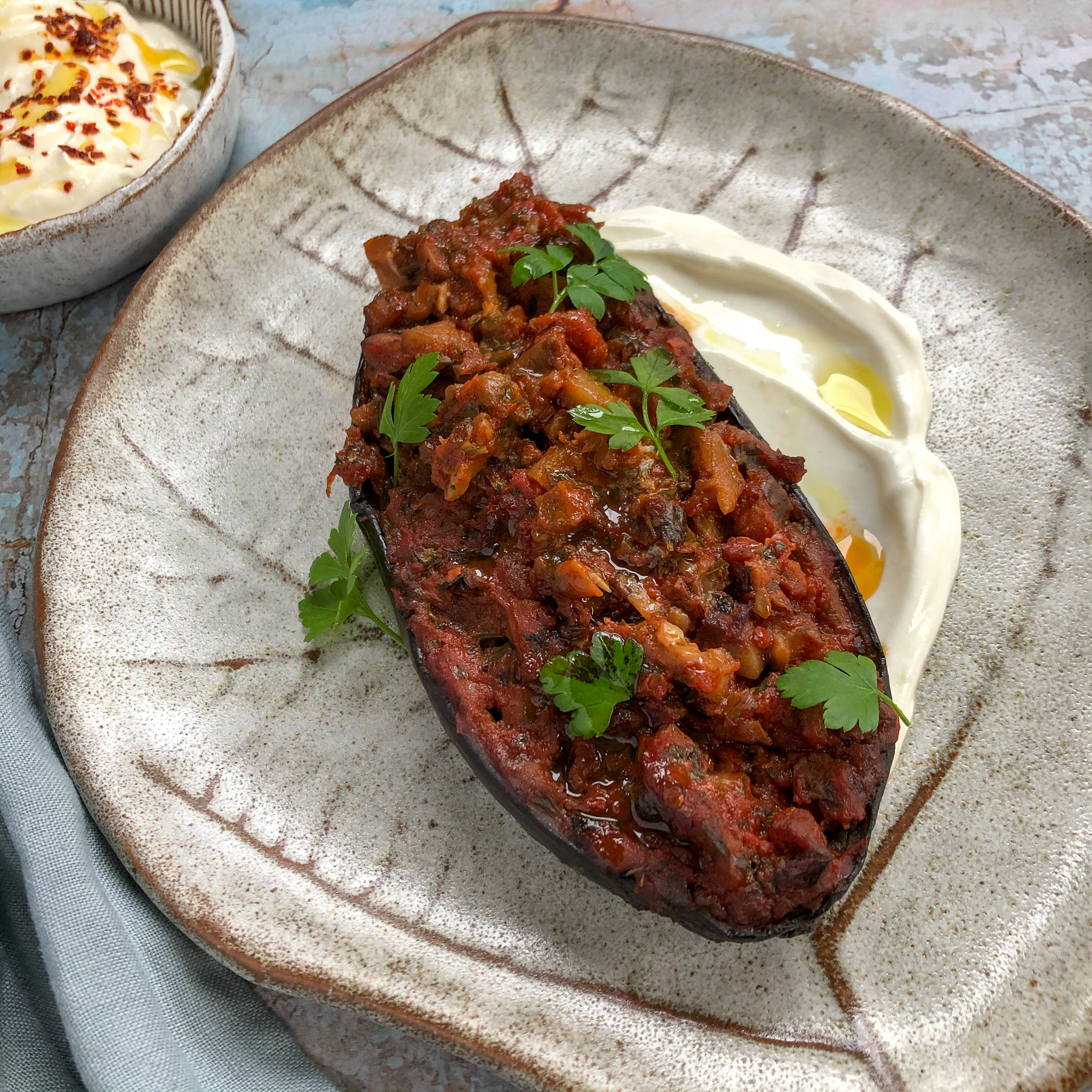 Half an aubergine baked with aubergine and tomato filling, on a bed of yoghurt.